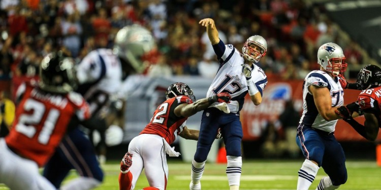 Sep 29, 2013; Atlanta, GA, USA; New England Patriots quarterback Tom Brady (12) throws while being hit by Atlanta Falcons linebacker Akeem Dent (52) in the first half at the Georgia Dome. Mandatory Credit: Daniel Shirey-USA TODAY Sports