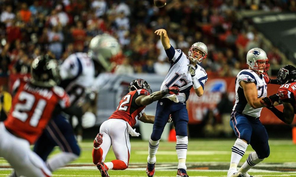 Sep 29, 2013; Atlanta, GA, USA; New England Patriots quarterback Tom Brady (12) throws while being hit by Atlanta Falcons linebacker Akeem Dent (52) in the first half at the Georgia Dome. Mandatory Credit: Daniel Shirey-USA TODAY Sports